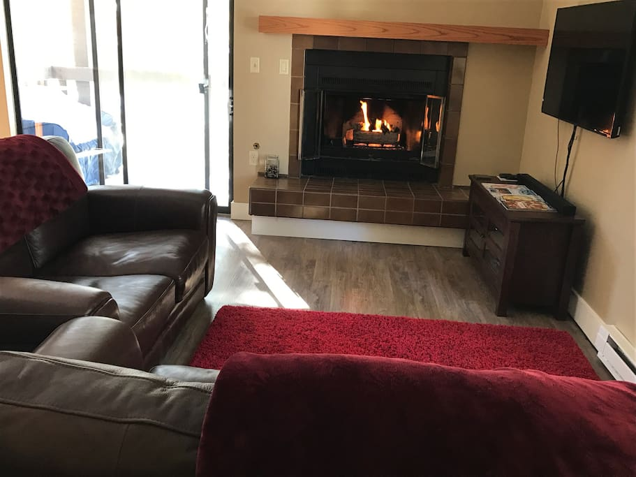 Spacious, bright living area with leather sofa and love seat.