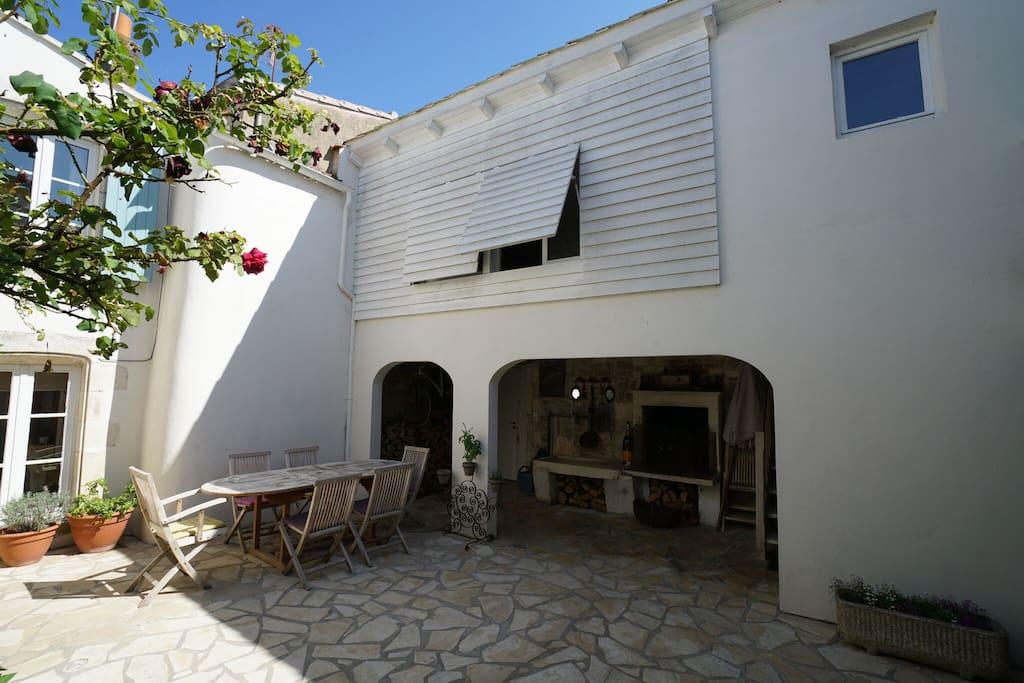 La cour avec à gauche la maison principale et à droite, sous le haut vent le barbecue. A l' étage, la quatrième chambre, son wc et sa salle de douche.