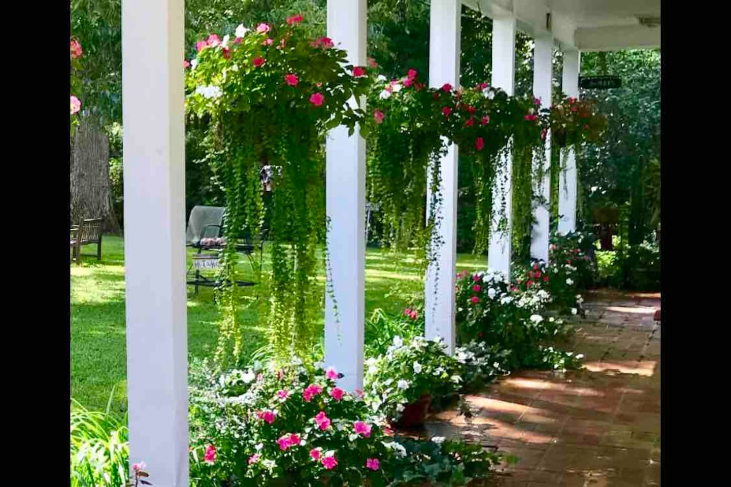 Hanging flower baskets grace the covered walkway entry to the Carriage House guest quarters.  Dreamy.