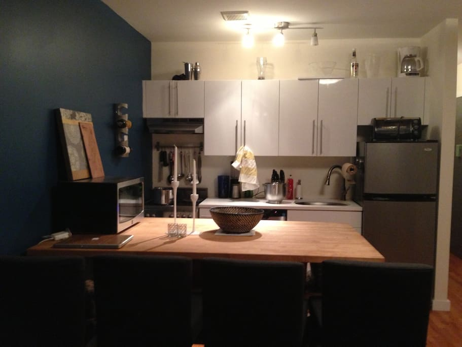 Spacious kitchen area with dishwasher, microwave, and toaster oven. Large eat-in island with four stools.
