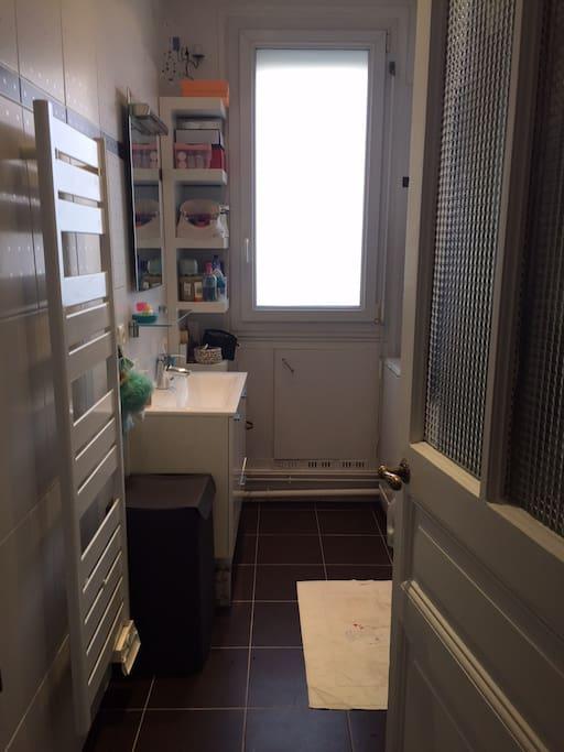 Salle de douche avec machine à laver et radiateur sèche serviettes