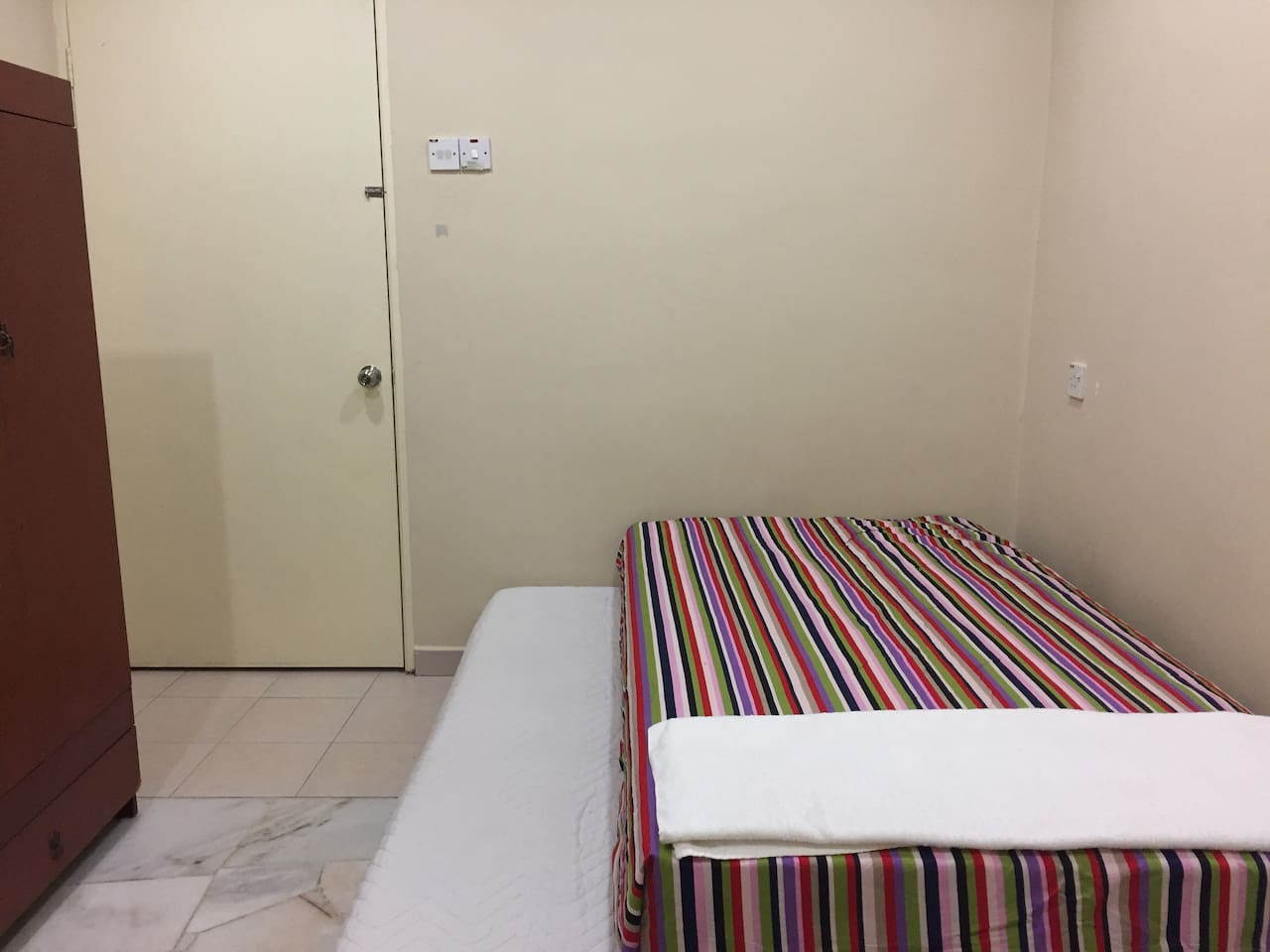 Bedroom with air conditioner and attached bathroom. Another single mattress can be provided if required.