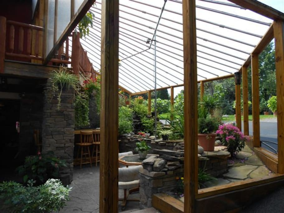 Greenhouse patio with waterfall and koi pond