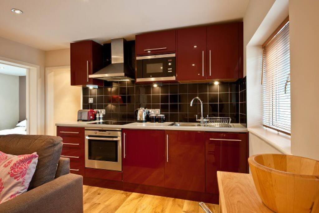 Modern kitchen, cooker, hob, microwave, fridge/freezer, dishwasher and washing machine.