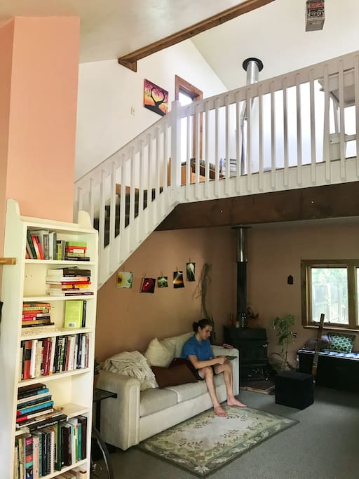 Downstairs living room with wood stove and upstairs living room/ yoga space