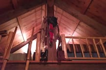 Sleeping loft with two full beds, and night stands, sconce lighting, open beam vaulted ceiling and view of LR. Loft access from lodge-pole pine ladder.