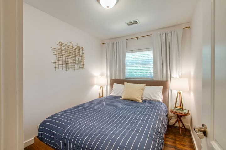 Bedroom 2 is bright and crisp with a comfy queen bed and blackout curtains for a restful night sleep after a fun night out in Nashville!