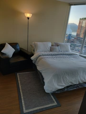 The master bedroom with its own bath and the Queen size bed specially prepared for your enjoyment and comfort. You are able to see the whole of beautiful Vancouver from inside your bedroom just looking through the windows only.
