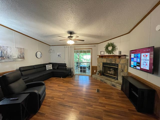 Living room with gas log fireplace and couch that converts into a queen bed (pullout). Recliner has massage controls. Large memory foam bean bag is stored behind recliner. TV is equipped with Roku and is logged into most streaming services.