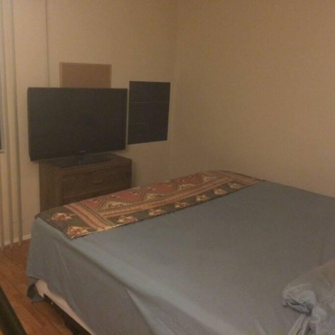 Queen bed, TV, corkboard