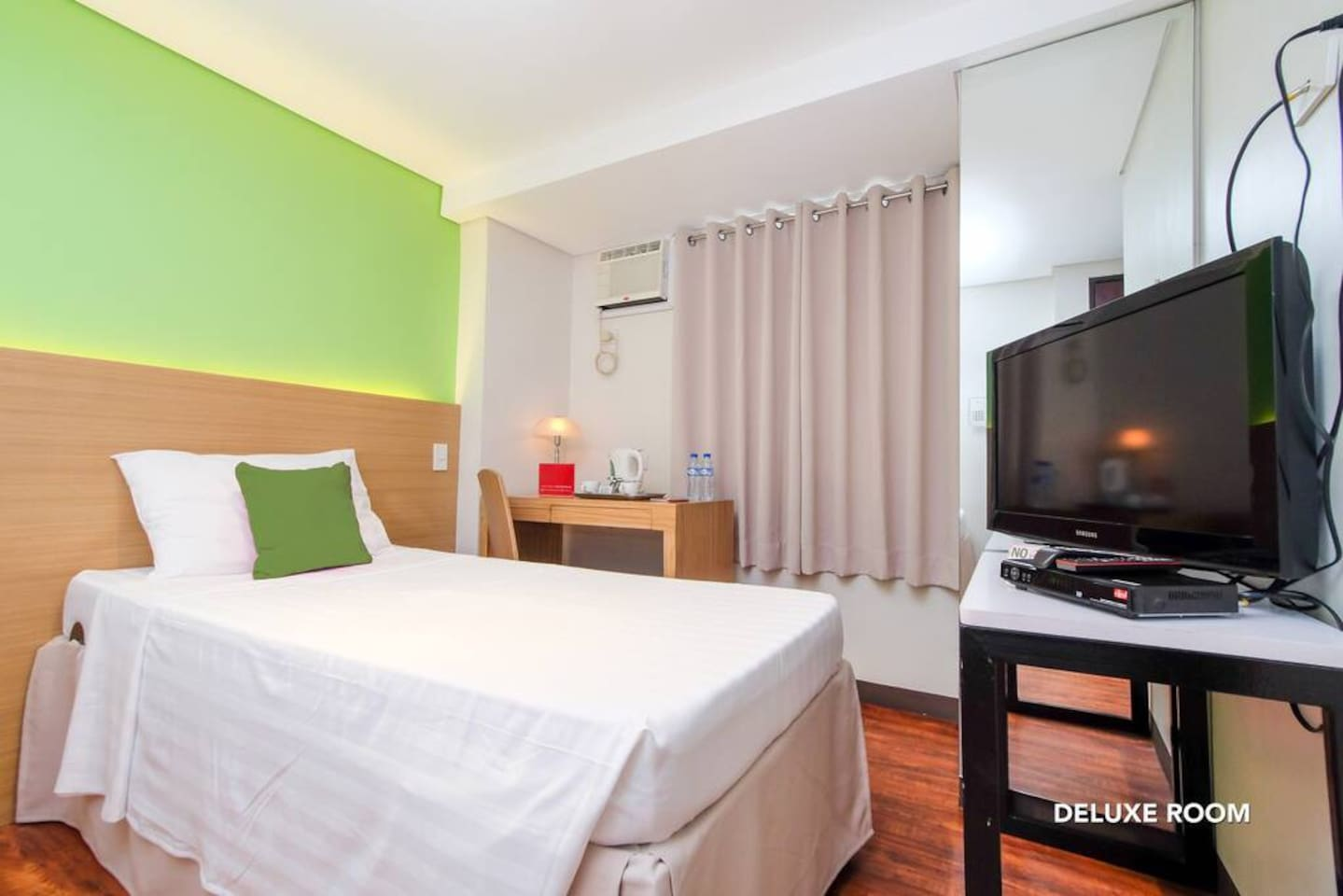 Interior of DeLuxe Twin Room at MySpace Hotel @BGC. Room amenities shown are desk, lamp shade, cable television, electric kettles with cups and free distilled water.