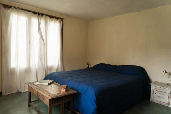 La habitación principal con cama doble y vistas al jardín.