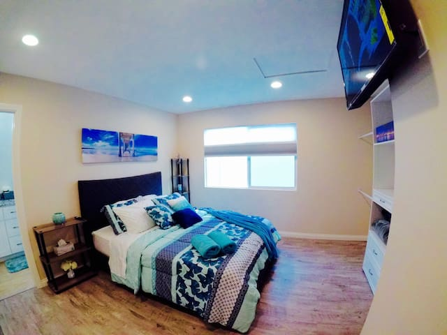 Master bedroom with queen size bed, Amazon Fire TV, and custom open closet. Our blinds also change from daytime to nighttime to allow natural sunlight in, or to keep it dark for your privacy