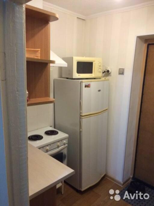 Небольшая кухня: плита, духовка, холодильник, микроволновая печь, электрический чайник, раковина.