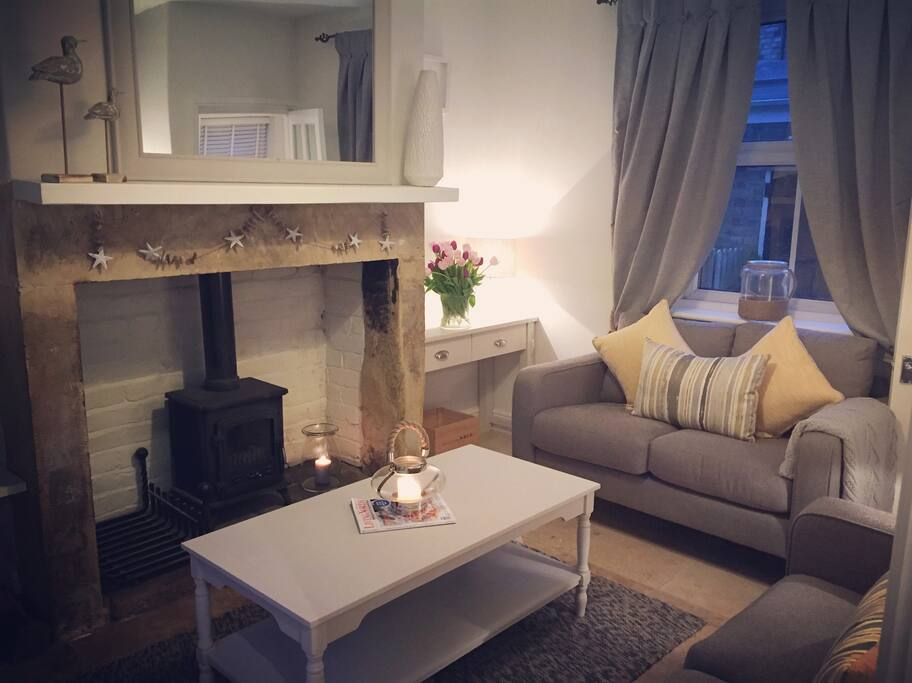 The cosy lounge has a log burning stove, smart tv and windows facing out on the courtyard garden and rear yard garden.