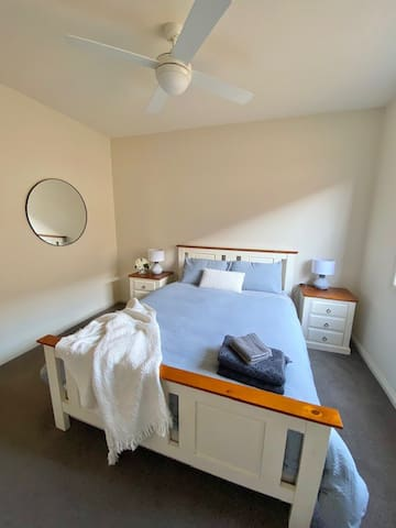 Queen bed with walk in robe and wall mounted TV.