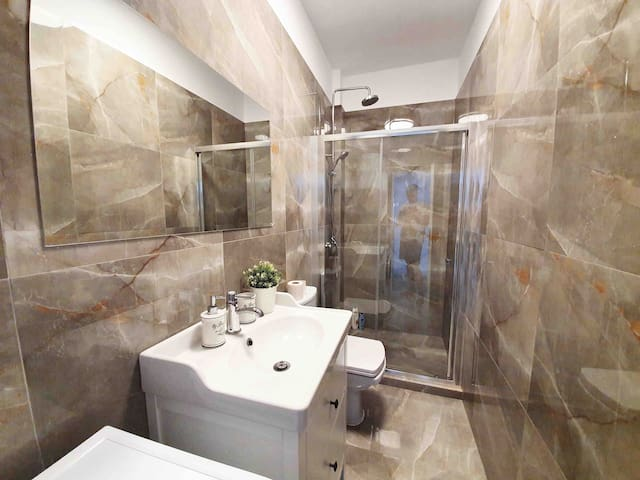 Marble bathroom with a shower with a washing machine