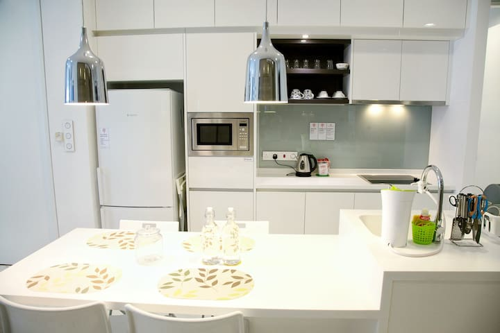 Kitchen fully equipped with appliances, utensils and cooking ware