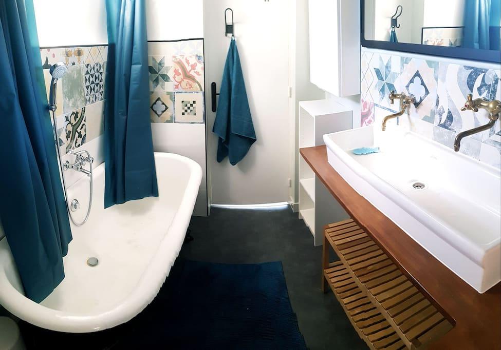 Salle de bain avec grande baignoire en fonte