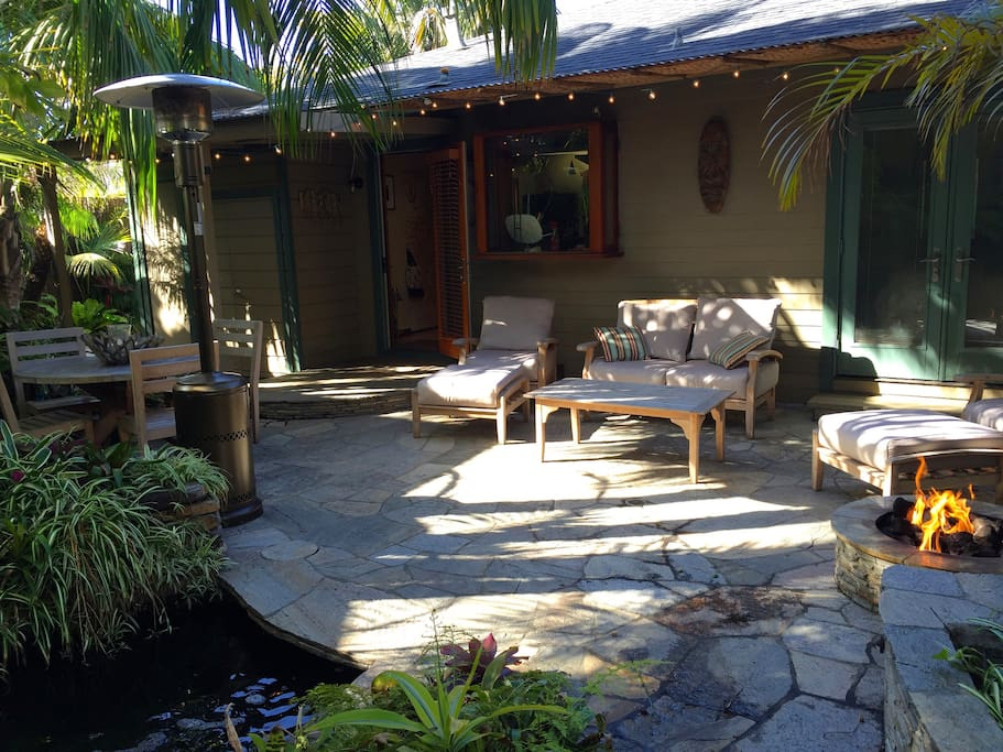 Back yard stone patio offers tranquil setting in lush tropical landscape with koi pond and water falls, cushioned teak lounge furniture, dining, fire pit, grill, and bamboo pavilion.