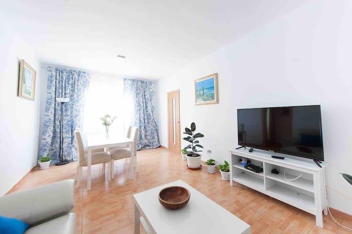 Spacious and sunny living room with a TV, where you can rest after a long day walk around the city!