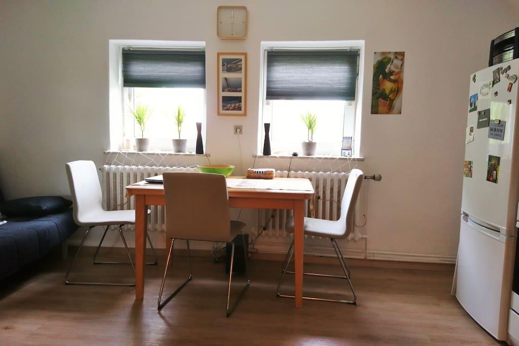 Wohnküche mit Esstisch und drei Stühlen, im Kühlschrank warten eine Flasche Sekt und reichlich Eiswürfel