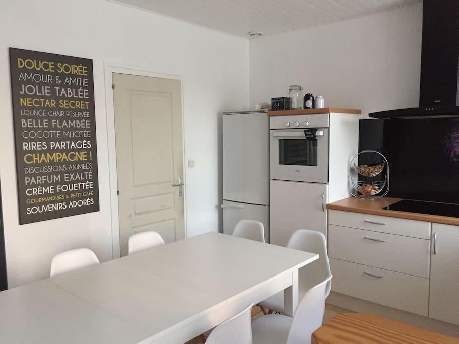 Cuisine ouverte sur salon avec plaques induction, frigo, four, micro-ondes, cafetière, grille-pain, bouilloire...