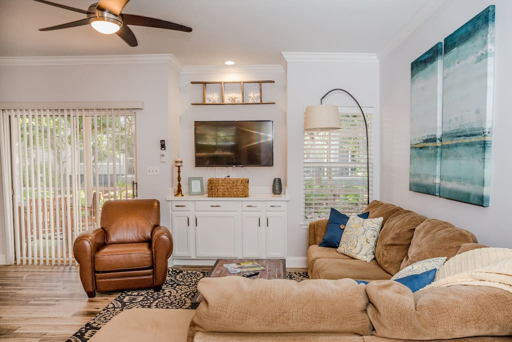 """50"""" TV and sliding glass door that leads to the huge screened-in patio"""