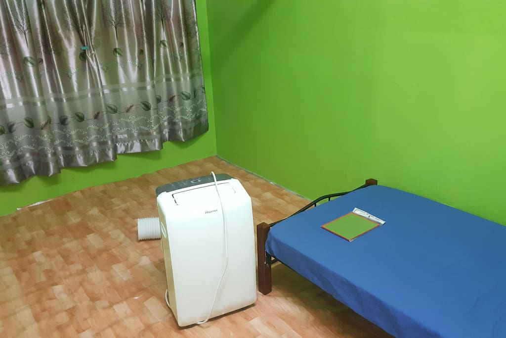 The room comes with a curtain and a portable air conditioner.