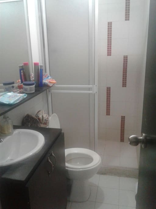 Baño, lavamanos, ducha con calentador eléctrico.
