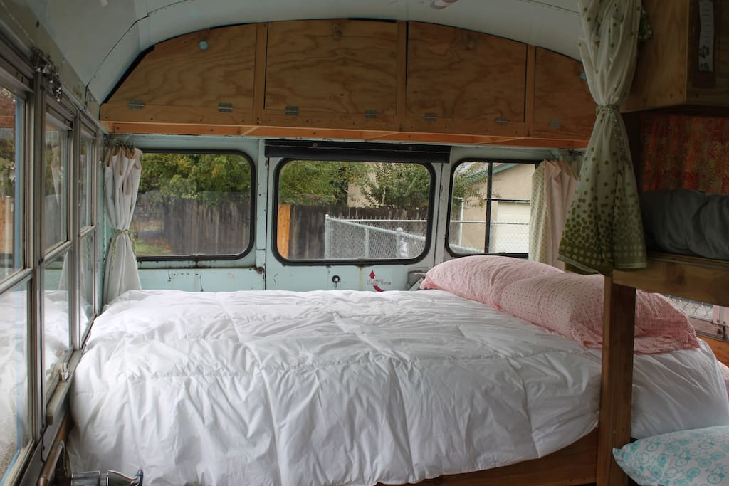 Queen bed with storage cubbies above.