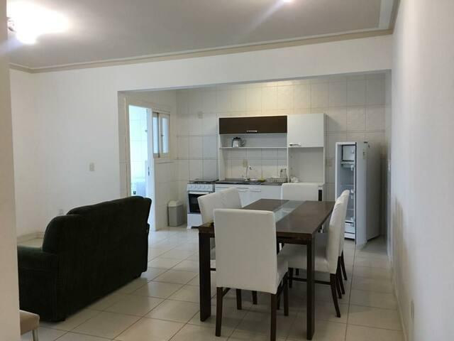 Sala de jantar, cozinha e sala de estar integrados bem iluminados e com muito espaço.