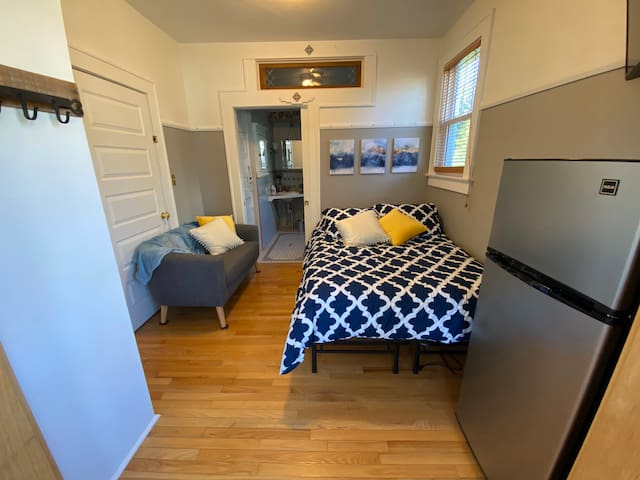 Full size bed, small couch, and fridge in guest space.