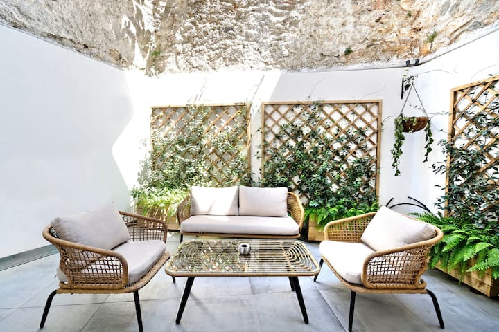The backyard patio has a seating spot with a table, the perfect place to relax after a full day visiting the city.