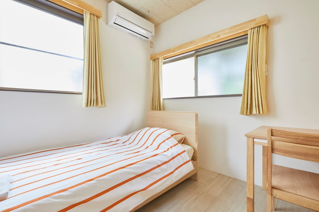 > A Private room with 1 bed, closet, chair, and table.