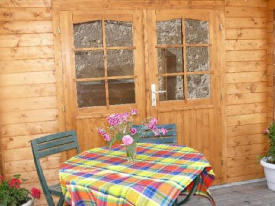 Terrasse avec cabane on y trouve salon de jardin, transats, barbecue