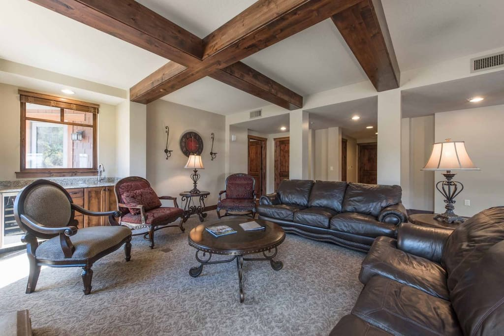 The living room is beautifully decorated in natural stone, rich hardwood, timber frame construction and features a wet bar with wine fridge.