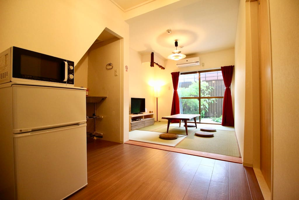 LIving room with kitchen. There're refrigerator, microwave, introduction heater, and kitchen tools.