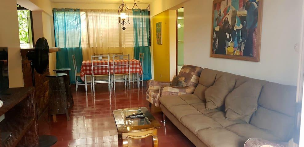 Un futon / canapé lit dans le salon, salle à manger pour 6, cuisine ouverte équipée.
