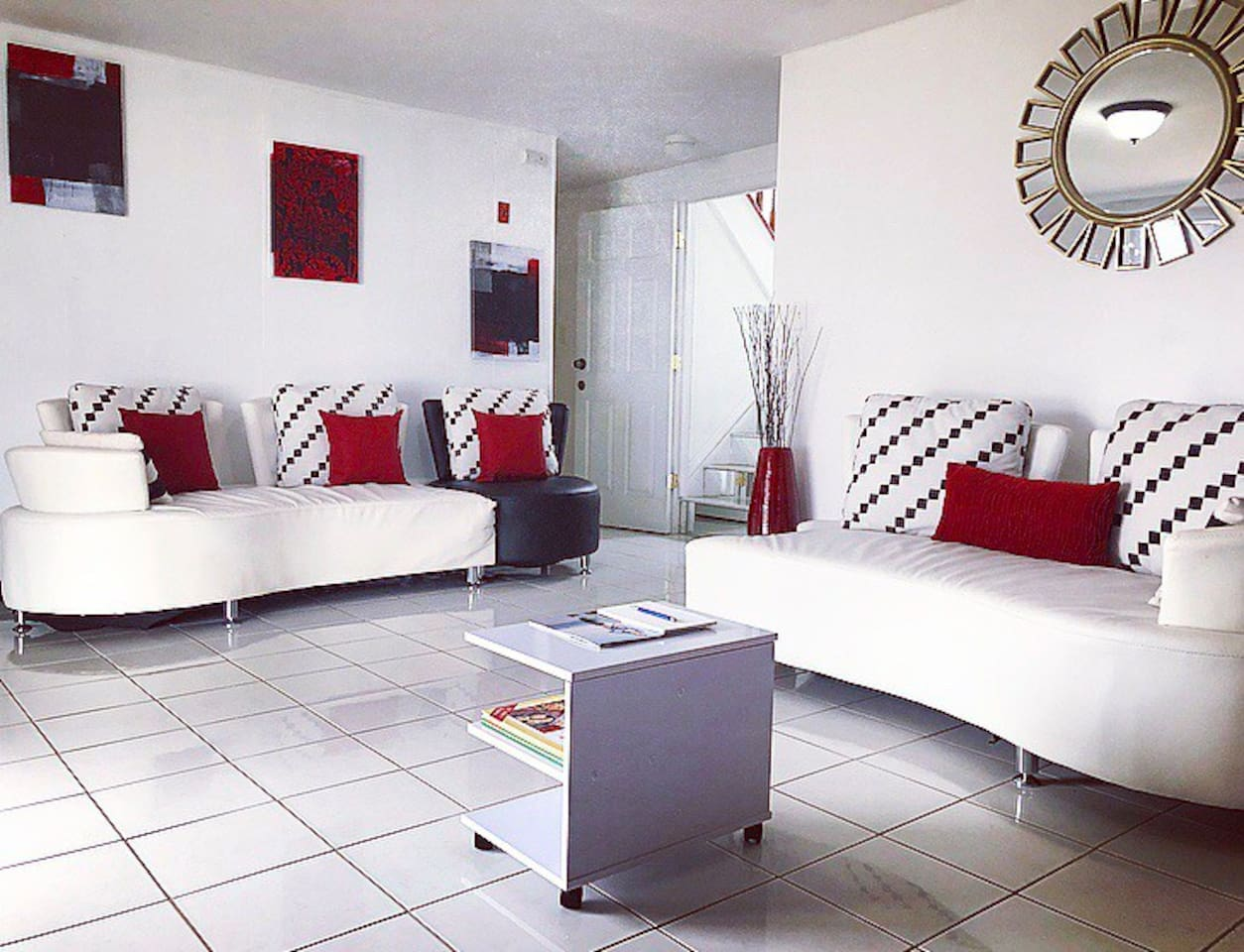 Living room designed with white leather swivel couches and Donna Karen pillows, ceramic tiles