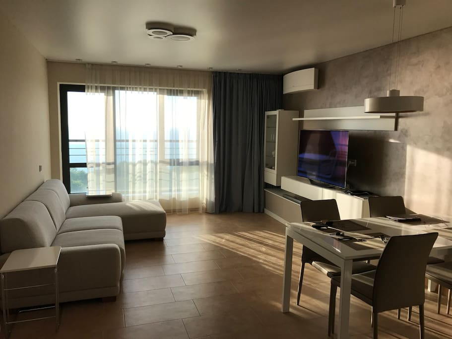 The living room with a TV and a balcony with an 180 degree view of the black sea.