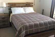 Room 2 is a warm room with a queen size bed.
