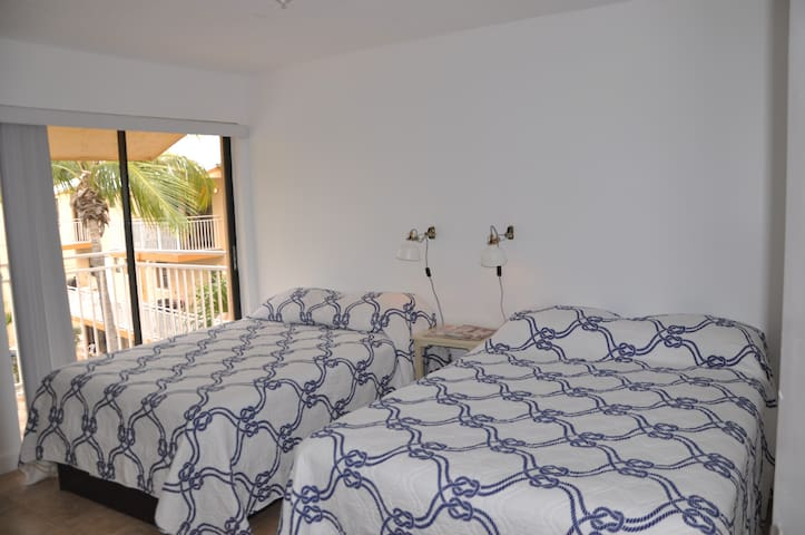 3rd Floor - Bedroom with 2 full beds, balcony and flat screen tv