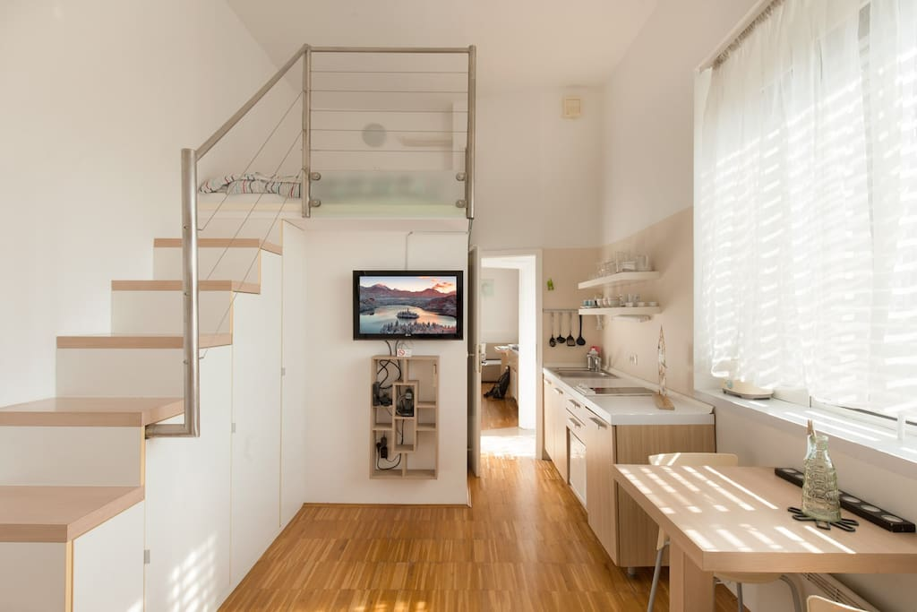 Apartment Urban 1 - kitchen with dining/ working table and a TV corner, double bed on the gallery