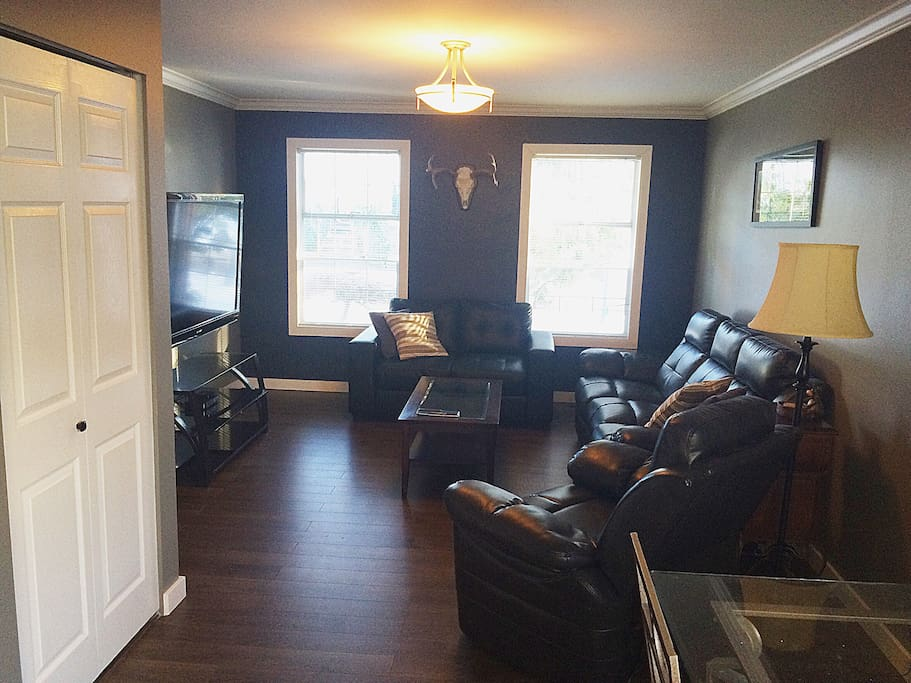 Large living room with 60 inch flatscreen tv, with Apple TV and wifi. Closet and dining table.