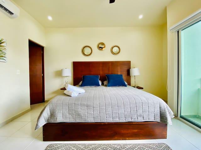 Recamara principal cuenta con cama king size con TV, A/C, closet completo y un baño. Esta area tiene una terraza con vista parcial a la alberca