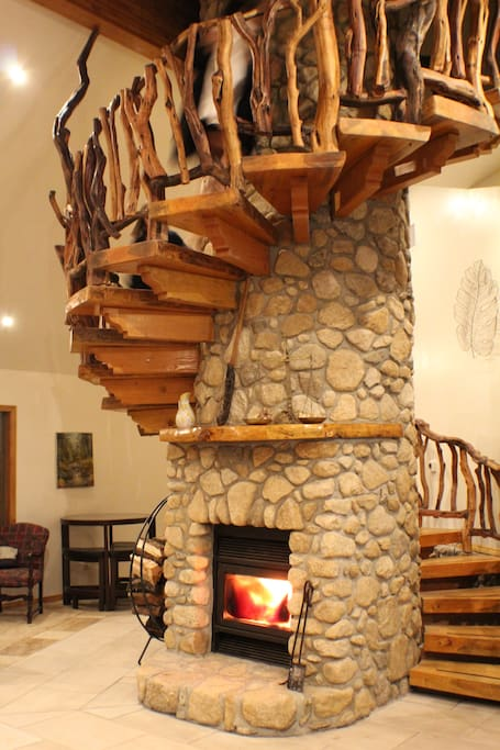 The iconic Manzanita spiral staircase and stone chimney is the centerpiece of the living room!