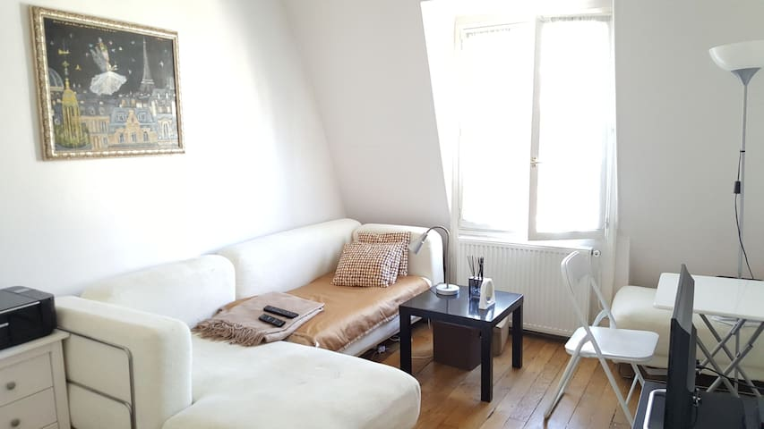 Spacy & cosy Living room/Salon with a sofa that can be used as a sleeping place for a 3rd person. There is also 3 tables for your stuff or to work on your PC. The TV set is just in front of the sofa.