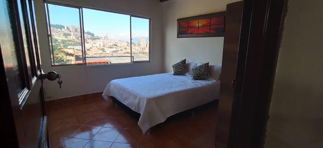 Una fresca brisa entra por esta ventana donde puedes observar toda la comuna 9 y como cae la tarde sobre las montañas de Medellín