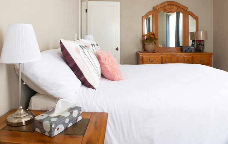 Front bedroom has a Queen size bed, nightstands with bedside lamps, alarm clock, closet and a dresser.  Room darkening curtains so you can sleep in!